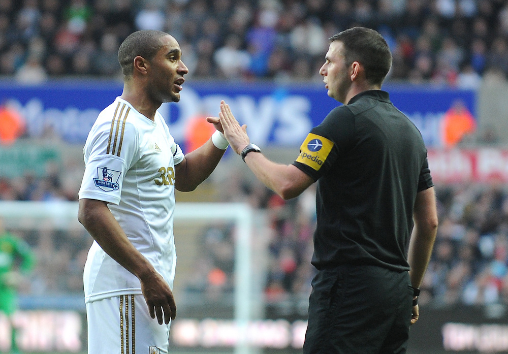 Referee Michael Oliver warns Swansea City's Ashley Williams after kicking the ball against his head ..Football - Barclays Premiership - Swansea City v Manchester United - Sunday 23rd December 2012 - The Liberty Stadium - Swansea..