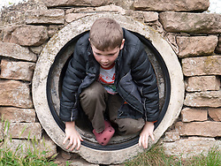 Boy coming out of playground tunnel