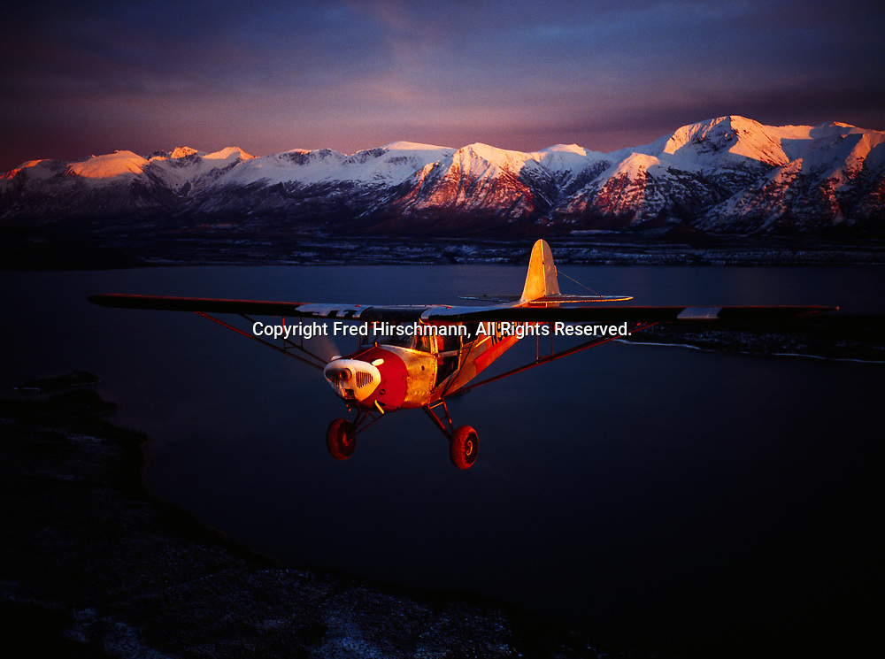 Leon Alsworth flying his Taylorcraft over Chulitna Bay of Lake Clark at sunset, Chigmit Mountains beyond, Lake Clark National Park and Preserve, Alaska.
