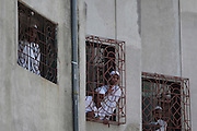 Youngsters attending a Muslim school peek out of the windows during a break.  The slum of Cheetah Camp on the outskirts of Mumbai, India is a predominantly muslim community on living on the fringe while the city continues to grow.
