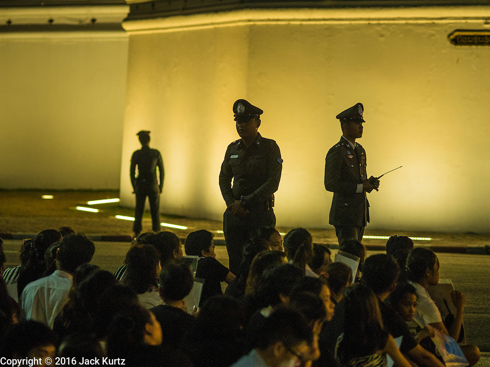 20 OCTOBER 2016 - BANGKOK, THAILAND: Royal Thai Police officers watch the crowd of mourners on Sanam Luang. The walls of the Grand Palace are behind the police officers. Sanam Luang, the Royal Ceremonial Ground, is packed with people mourning the Monarch's death. The King died Oct. 13, 2016. He was 88. His death came after a period of failing health. Bhumibol Adulyadej was born in Cambridge, MA, on 5 December 1927. He was the ninth monarch of Thailand from the Chakri Dynasty and is also known as Rama IX. He became King on June 9, 1946 and served as King of Thailand for 70 years, 126 days. He was, at the time of his death, the world's longest-serving head of state and the longest-reigning monarch in Thai history.        PHOTO BY JACK KURTZ