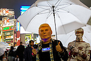 A man wearing a Donald Trump mask celebrates Halloween, despite the rain, Shibuya, Tokyo, Japan. Friday October 28th 2016 Halloween celebration in Japan have grown massively in the last few years. To ensure the safety of the crowds in Shibuya this year, the police closed several roads leading to the famous Hachiko Square, allowing costumed revellers to spread over a larger area.