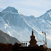 Trekkers stand at the Hillary Memorial Chorten above Namche Bazaar en route to Mount Everest, Nepal. The imposing South Face of Lhotse and Nuptse, as well as the summit of Everest, rise behind.