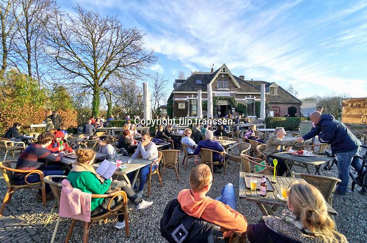 Nederland, Ooij, 24-2-2019 Vanwege het mooie weer is het druk op het terras van huiskamercafe oortjeshekken. Op deze mooie en zachte dagt trekken veel mensen, dagjesmensen, fietsers, er op uit om te genieten van het mooie weer . Het dijkcafe is een toeristische trekpleister voor wandelaars aan de dijk in de ooijpolder . Foto: Flip Franssen