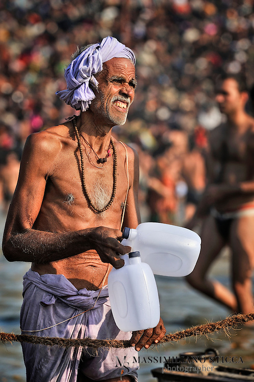 A pilgrim fills canisters with holy water from the Ganges..