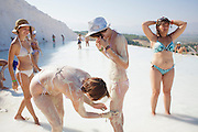 Tourists aplying calcium-rich mud from the pools in Pamukkale. The hard, white mineral deposits, which from a distance resemble snow, are caused by the high mineral content of the natural spring water which runs down the cliff and congregates in warm pools on the terraces. This is such a popular tourist attraction that strict rules had to be established in order to preserve its beauty, which include the fact that visitors may no longer walk on the terraces. Those who want to enjoy the thermal waters, however, can take a dip in the nearby pool, littered with fragments of marble pillars.