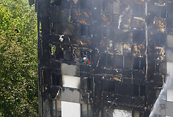 A firefighter photographs damage after a fire engulfed the 24-storey Grenfell Tower in west London.