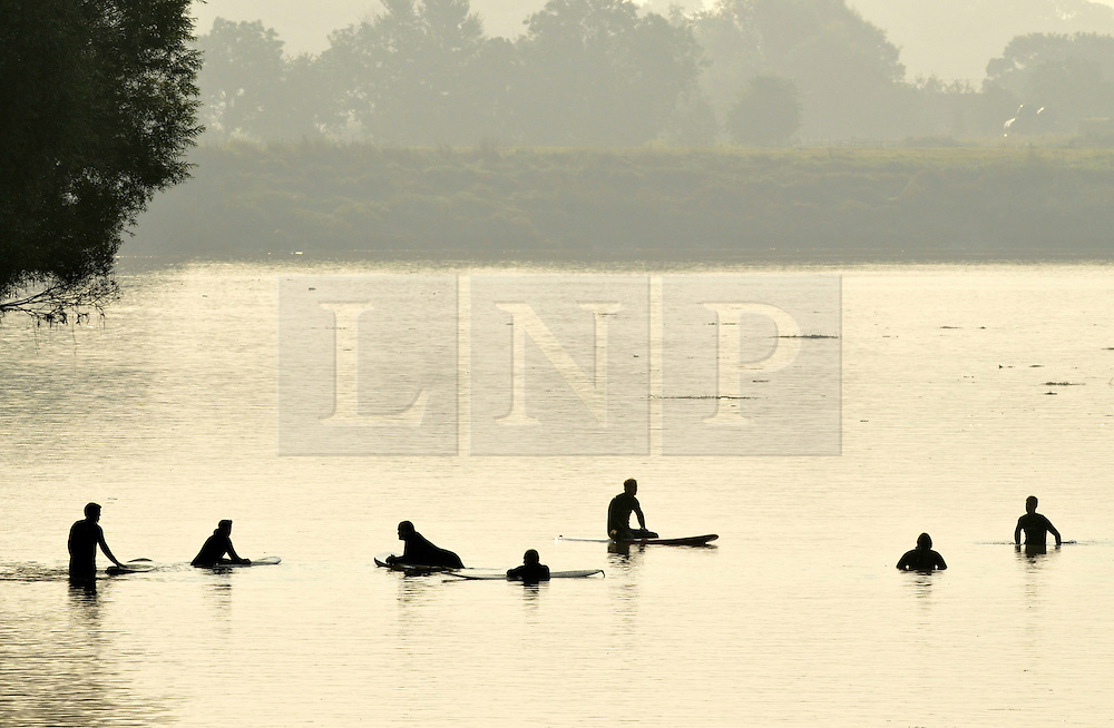 © Licensed to London News Pictures. 10/09/2014. Minsterworth, Gloucestershire, UK.  Surfers and kayakers try to catch this morning's Severn Bore by the Severn Bore Inn at Minsterworth. Photo credit : Simon Chapman/LNP