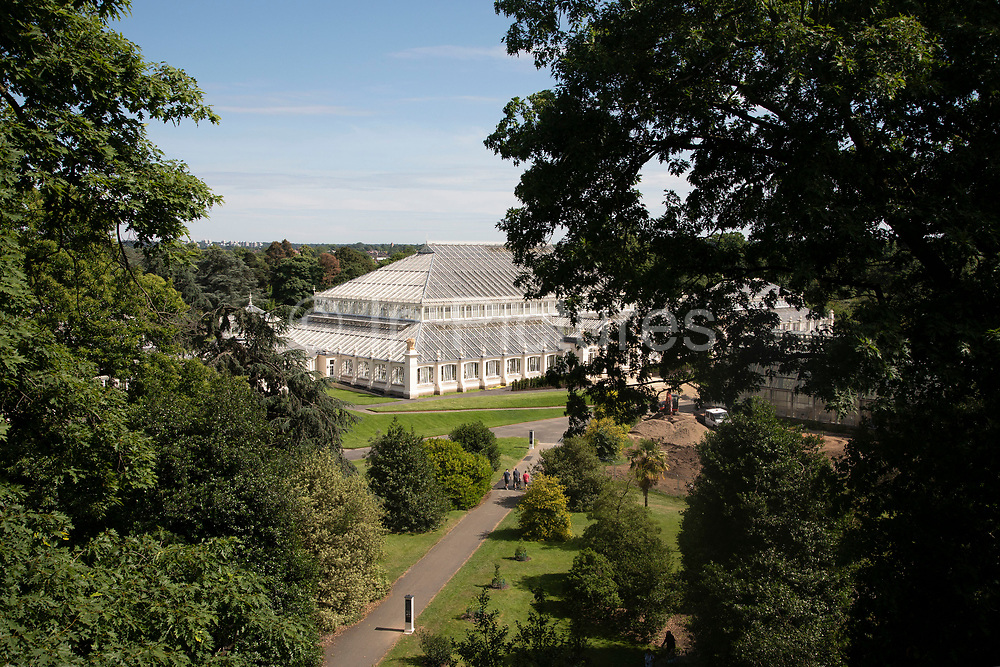 Aerial view of the newly refurbished Temperate House at Kew Gardens in London, United Kingdom. The Royal Botanic Gardens, Kew, usually referred to simply as Kew Gardens, are 121 hectares of botanical gardens and glasshouses between Richmond and Kew in southwest London. It is an internationally important botanical research and education institution with 700 staff, receiving around 2 million visitors per year. Its living collections include more than 30,000 different kinds of plants.