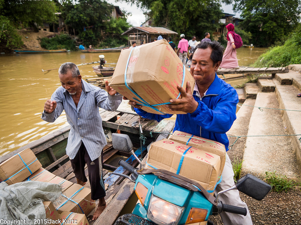 16 JUNE 2015 - SUNGAI KOLOK, THAILAND:  A motorcycle picks up a load of Malaysian palm oil at an informal border crossing on the Thai - Malaysia border in Sungai Kolok. The border between Thailand and Malaysia in Sungai Kolok, Narathiwat, Thailand. Thai and Malaysians cross the border freely for shopping and family visits. The border here is the Kolok River (Sungai is the Malay word for river).        PHOTO BY JACK KURTZ