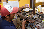 Mexican man making jewellery from Amber, polishing the stones in a small workshop, San Cristobal de las Casas, Chiapas, Mexico.