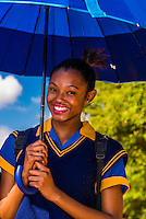 A school girl carries an umbrella to shield herself from the sun, Mkize Street, Rockville, Soweto, Johannesburg, South Africa.