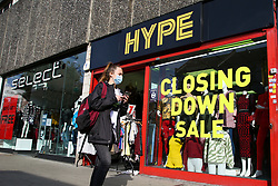 © Licensed to London News Pictures. 19/10/2020. London, UK. A woman wearing a face covering in north London walks past 'CLOSING DOWN SALE' sign in a shop window which is closing due to coronavirus crisis. According to the figures, revealed by the Local Data Company and advisory firm PricewaterhouseCoopers (PwC), a total of 11,120 shops on UK high streets closed in the first half of this year due to the coronavirus lockdown.  Photo credit: Dinendra Haria/LNP