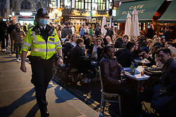 © Licensed to London News Pictures. 16/04/2021. London, UK. Police patrol as members of the public enjoy food and drink in Soho in Central London. Earlier this week Lockdown restrictions were eased to allow non essential retail and outdoor dining to reopen. Photo credit: George Cracknell Wright/LNP