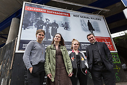 © Licensed to London News Pictures. 23/05/2016. LONDON, UK.  Becky Warnock, Abbie Gillgan, Bethan Lant (all from East End Women's Collective) with Priest-in-Charge of St George-in-the-East church, Angus Ritchie unveil a billboard located opposite the Jack the Ripper museum in Cable Street, Tower Hamlets, advertising a new pop-up museum, 'East-End Women: The Real Story'. Following and opposition and protests against the controversial Jack the Ripper museum, which had promised to celebrate east end women, but activists opposed and claimed glorified violence against women, the museum is a response by the East End Women's Collective, with funding from 38 Degrees members, which aims to celebrate east end women who have stood up for women's rights and against violence. The museum will open at St George-in-the-East church from 26th May to 9th July.  Photo credit: Vickie Flores/LNP