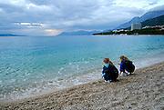 Two children (9 years old, 5 years old) squatting on beach at sunset. Makarska, Croatia