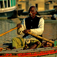 Asia, India, Varanasi. A man rows quietly on the Ganges River at Varanasi.