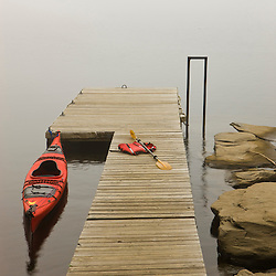 A kayak next to a boat dock on a misty morning on Lake Francis in Pittsburg, New Hampshire.