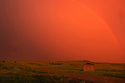 Rainbow and setting sun during prairie storm. West Block<br /> Grasslands National Park<br /> Saskatchewan<br /> Canada