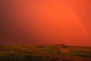 Rainbow and setting sun during prairie storm. West Block<br /> Grasslands National Park<br /> Saskatchewan<br /> Canada