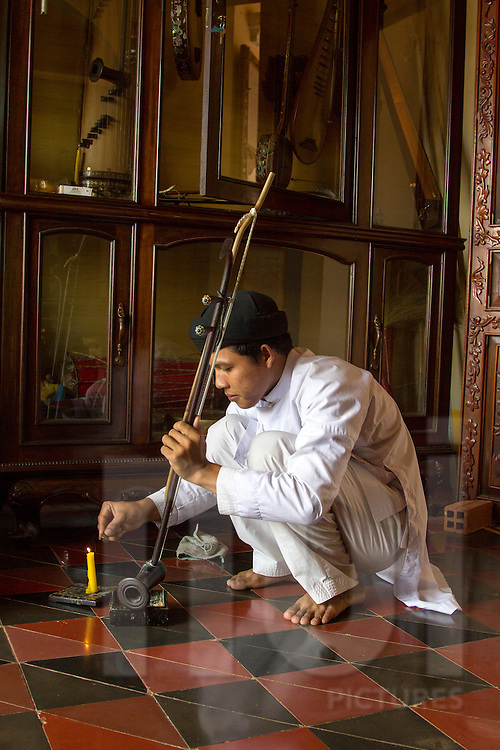 A man fixes a music instrument in Cao Dai Temple, Tay Ninh, Vietnam, Southeast Asia
