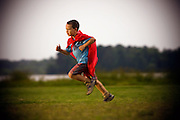 A young boy wearing a red cape runs through a field.