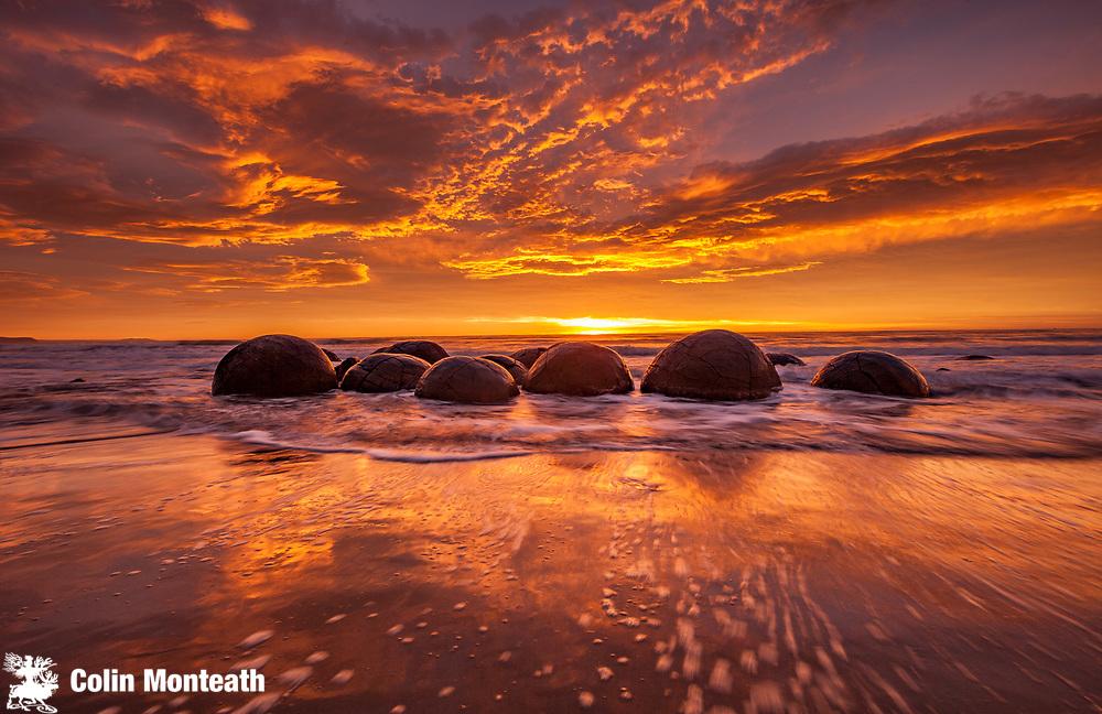 Moeraki boulders at dawn as SW front passes overhead, near Oamaru, Otago,