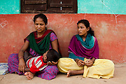 Manisha Sunar (left), 18, cradles her 2 year old son, as her husband's niece Pramila Bhujel, 13, sits next to her at the information center near their home in Lekhapharsa vilage, Surkhet district, Western Nepal, on 30th June 2012. Manisha was married off when she was 14 but secretly used contraceptives with the help of her husband's sister. When he found out, he forced her to stop and she was soon pregnant with no money to terminate it. She's now 8 months pregnant again even though her husband neglects and abuses her and her son. He also mistreats Pramila and earlier this year, a fellow villager secretly married Pramila off to a man in his mid-20s but the marriage was annulled the day after when her uncle, Manisha's husband found out and wrestled her back. Now, Pramila is still mistreated by her uncle and is considered a divorcee since she spent one night with the man she was married to, but she is back in school and has ambitions to become a nurse. In Surkhet, StC partners with Safer Society, a local NGO which advocates for child rights and against child marriage. Photo by Suzanne Lee for Save The Children UK