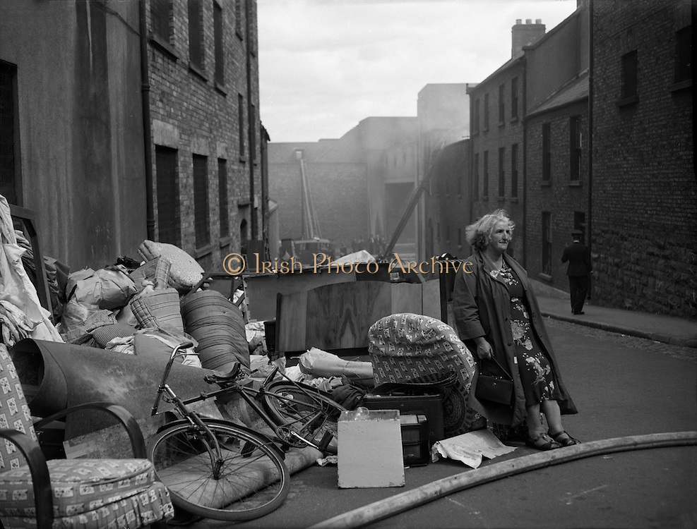 Some housing in Dublin was very old and dilapidated and there were several collapses. This lady and her belongings await rehousing. .05.07.1961