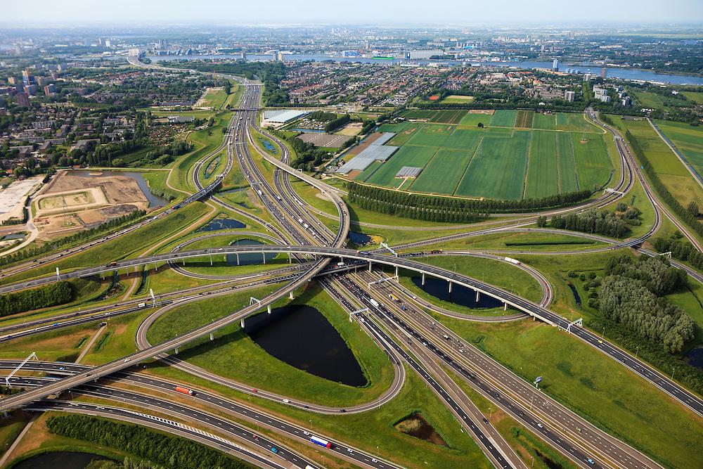 Nederland, Zuid-Holland, Ridderkerk, 23-05-2011; Knooppunt Ridderkerk, verkeersknooppunt A15 / A16, bijgenaamd 'Ridderster'. Klaverblad met opritten, afritten en fly-overs. De waterpartijen zijn kunstmatige aangelegd en kunnen dienen als bluswater ingeval calamiteiten. Maas en Van Brienenoordbrug aan de horizon..Ridderkerk junction, junction A15 / A16, nicknamed 'Ridder star'.  Cloverleaf type junction, with ramps, exit ramps and flyovers. The ponds are man-made and the water can be used for  firefighting in case of emergencies..luchtfoto (toeslag), aerial photo (additional fee required).copyright foto/photo Siebe Swart