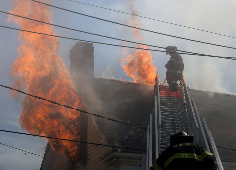 Milton, MA 03/08/2012.A Quincy firefighter swings his axe to ventilate the roof while fighting a 3 alarm house fire at 589 Adams St. in Milton on Thursday afternoon..Alex Jones / www.alexjonesphoto.com