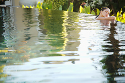 Portrait of young woman in an exotic swimming pool resting