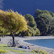 Cyclists relax on the water front at Lake Wanaka. Wanaka is  a year round destination set against the pristine alpine backdrop of Mount Aspiring National Park in Central Otago. South Island, New Zealand. 1st April 2011. Photo Tim Clayton.