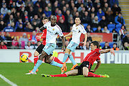 West Ham's Carlton Cole is tackled by Cardiff's Mark Hudson .Barclays Premier league, Cardiff city v West Ham Utd match at the Cardiff city Stadium in Cardiff, South Wales on Saturday 11th Jan 2014.<br /> pic by Andrew Orchard, Andrew Orchard sports photography.