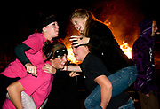 """NEWS&GUIDE PHOTO / PRICE CHAMBERS<br /> From top left, clockwise, Rebikita Mortensen, Mackenzie Binger, Maddy Wigg and Jenna Stafford have an impromptu chicken fight at the Jackson Hole High School homecoming bonfire on Wednesday night. Wigg says she likes the atmosphere of homecoming. """"It unites us for the next year,"""" she said. """"It brings the black and white together."""""""