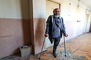 """Alexander Alexaninan, a 62 years old man, father of three children from Aygestan, which is in the province of Askeran in Nagorno Karabakh region, says that he will return back to Nagorno Karabakh should there be an opportunity. He was 34 of his age when he lost his leg in 1992 when an Azerbaijani artillery shell hit him in the frontline. He has been given shelter at the previously abandoned building of """"SOVIET Hotel"""" in Metsamor. His wife is now in Stepanakert with their 24 years old son who is studying at the moment he said. He is worried about their daughters one of whose husband is gone missing since the recent war. According to IOM (International Organisation for Migration) as of Dec 2020 - an estimated 92 639 people alone were displaced as a result of military operations in areas bordering Azerbaijan due to the 44 days of war over the region of Nagorno-Karabakh. (Photo/ Vudi Xhymshiti)"""