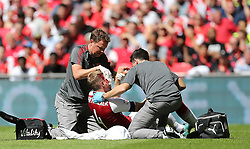 Arsenal's Per Mertesacker receives treament before going off injured against Chelsea