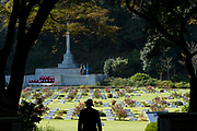 Silhouette of a man taking a last look at the Hodogaya, Commonwealth War Graves Cemetery in Hodogaya, at the end of the Remembrance Sunday ceremonies.Yokohama, Kanagawa, Japan. Sunday November 11th 2018. The Hodagaya Cemetery holds the remains of more than 1500 servicemen and women, from the Commonwealth but also from Holland and the United States, who died as prisoners of war or during the Allied occupation of Japan. Each year officials from the British and Commonwealth embassies, the British Legion and the British Chamber of Commerce honour the dead at a ceremony in this beautiful cemetery. The year 2018 marks the centenary of the end of the First World War in 1918.