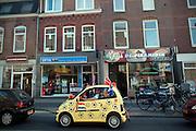 Een man staat met een geheel gepimpte brommobiel in het teken van het WK voetbal 2010 te wachten op de Amsterdamsestraatweg in Utrecht