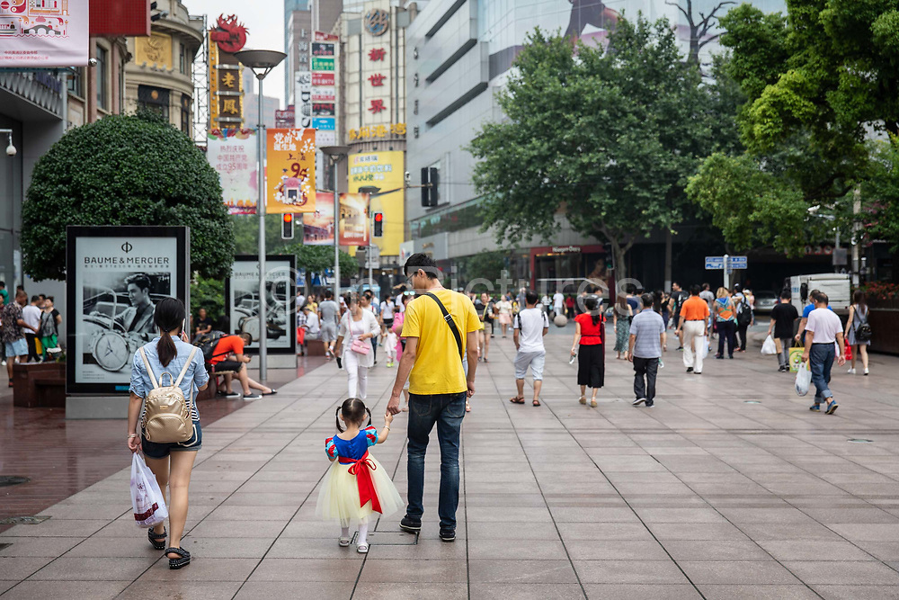 A young girl wearing a Snow White dress walks down Nanjing Road shopping district with her parents in Shanghai, China, on Sunday, July 3, 2016.