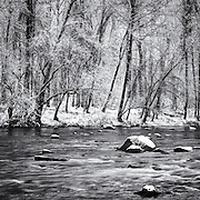 Snow and riverbank on the Patapsco River at Oella, Maryland. A black and white photograph.