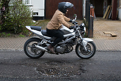 A motorcyclist, vulnerable to uneven road surfaces, swerves around a pothole, one of a series on Sidmouth Road in Willesden Green as the recent cold, wet weather has given rise to the increase in potholes and road surface deterioration in London. London, March 28 2018.