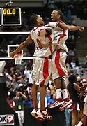 Minneapolis, MN - MN State high school basketball tournament at the Target Center. Minneapolis Patrick Henry High School players leap into the air in celebration following their victory over Sauk-Rapids-Rice in the Class 3A final, winning their fourth state title in a row.