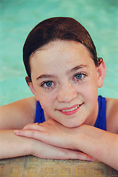 Portrait of young girl with learning disabilities resting on side of public swimming pool,