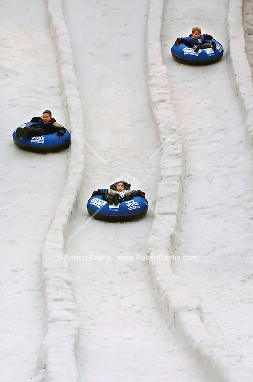 Children ride down a 28' tall, 225' long tubing hill at the Winter Blast Festival held in downtown Detroit, MI Friday, Feb. 3, 2006. Warm weather foiled many plans to make snow for the festival which was to include many winter activities such as dog sledding and snowshoeing. (Robert Caplin For The New York Times)..