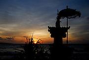 Small shrine and symbolic umbrella silhouetted against setting sun, Jimbaran Bay, Bali, Indonesia. Jimbaran Bay was the location of the second Bali terrorist bombing on October 2, 2005.
