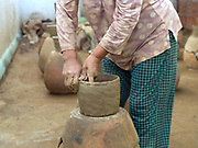 A Hindu Cham woman makes a ceramic pot using a traditional method in the famous pottery village of Bau Truc in Central Vietnam. Cham potters do not use a wheel to make pots, instead clay is pressed into shape using the hands. Layers of clay are added to the original piece and the potter moves around the object, pressing the clay into the desired shape. They are then put directly in the sun and completely bone dried, making them ready to be fired. Firing is done in an open pit with temperatures going up to 800 degree Celcius. The pots are arranged together and covered with layers of rice straw, which is set on fire.
