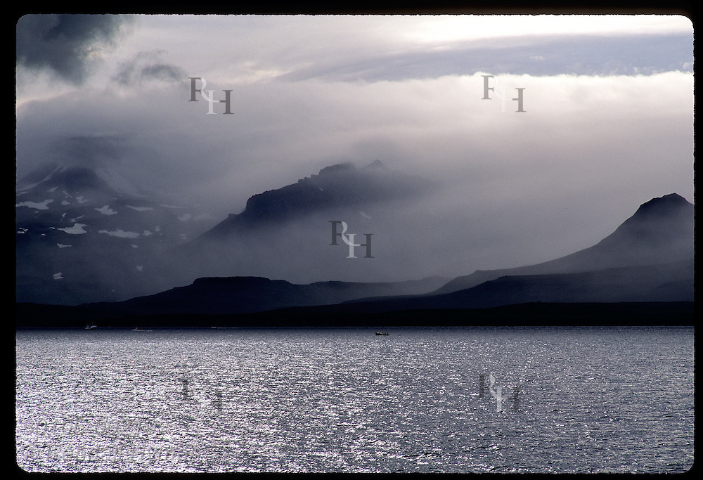Clouds shroud mountains that dwarf fishing boat on a summer day along Snaefell Peninsula. Iceland