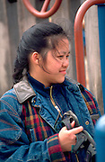 Asian woman age 15 hanging out at park. In the Heart of the Beast May Day Festival and Parade Minneapolis  Minnesota USA
