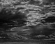 Sun shining through storm clouds across a grey sea.